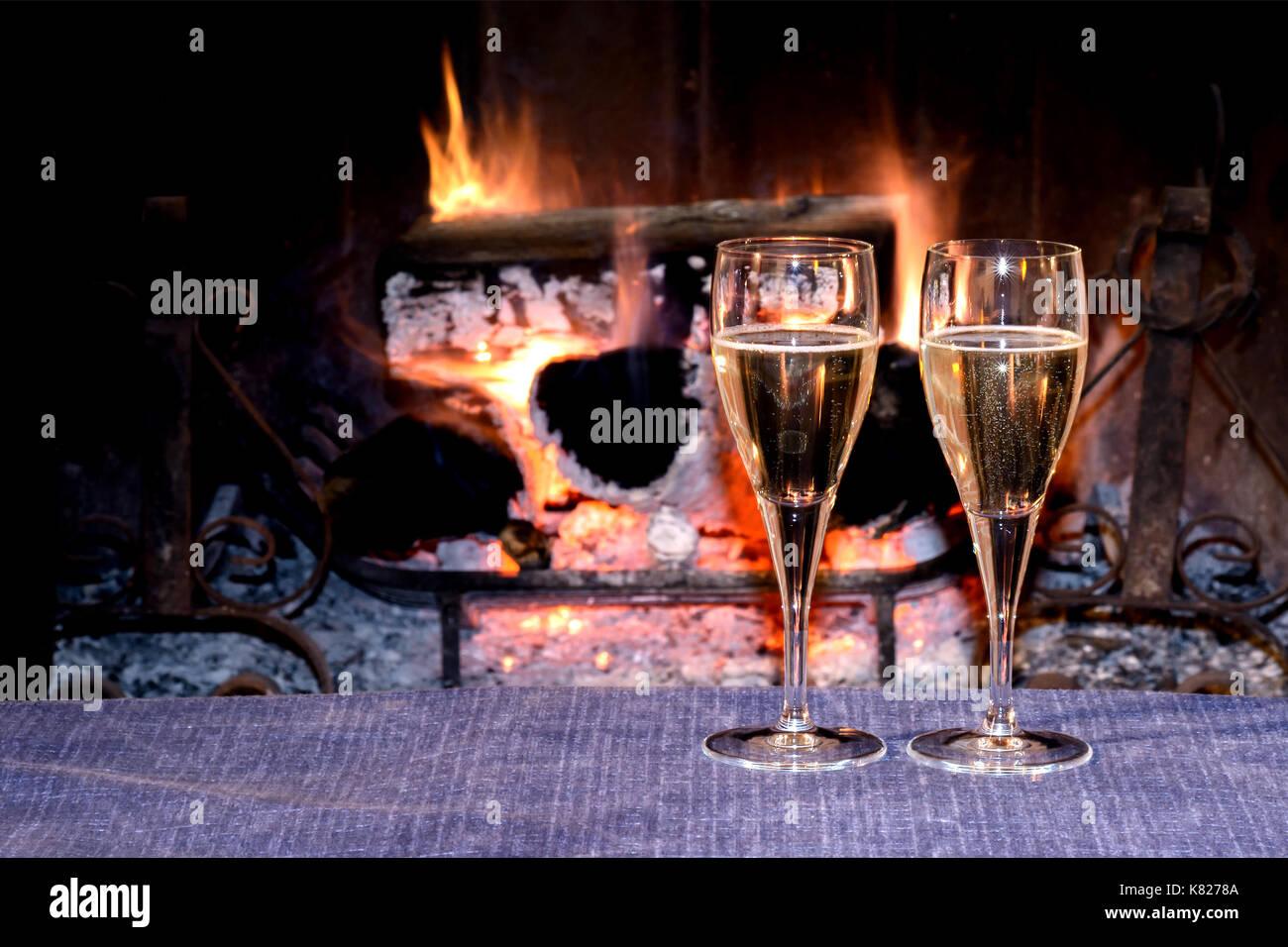 zwei gl ser champagner vor dem brennenden kamin einen romantischen abend mit schatz zu feiern. Black Bedroom Furniture Sets. Home Design Ideas