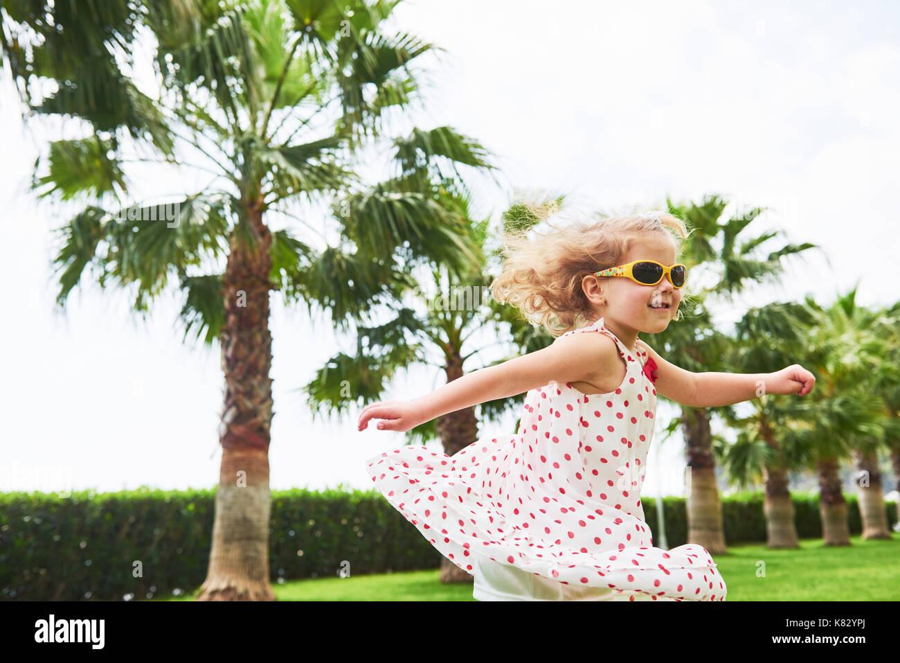 Baby Mädchen in einem Park in der Nähe von Bäumen. Stockbild