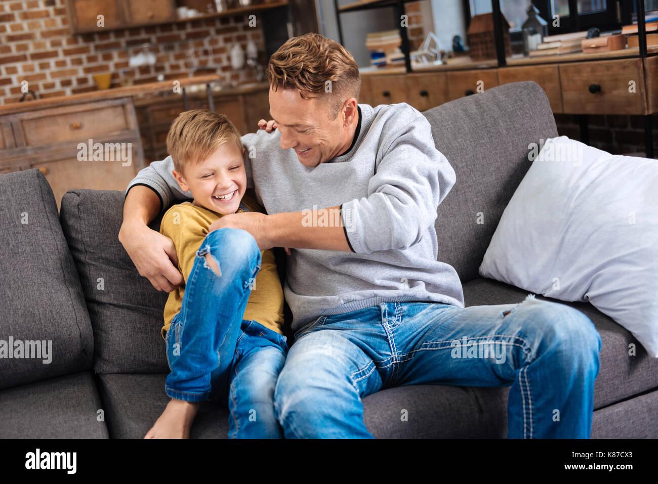 Liebevoller Vater kitzeln seinem kleinen Sohn auf dem Sofa Stockbild