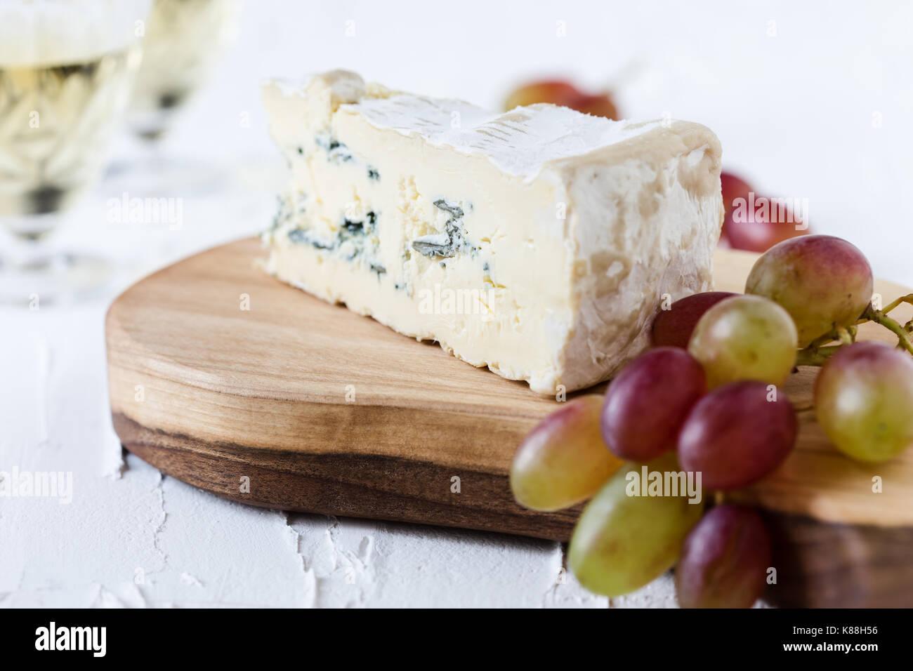 Blauschimmelkäse mit frischen Trauben und zwei Gläser Weißwein auf rustikalen Schneidbrett, Käseplatte serviert. Stockbild