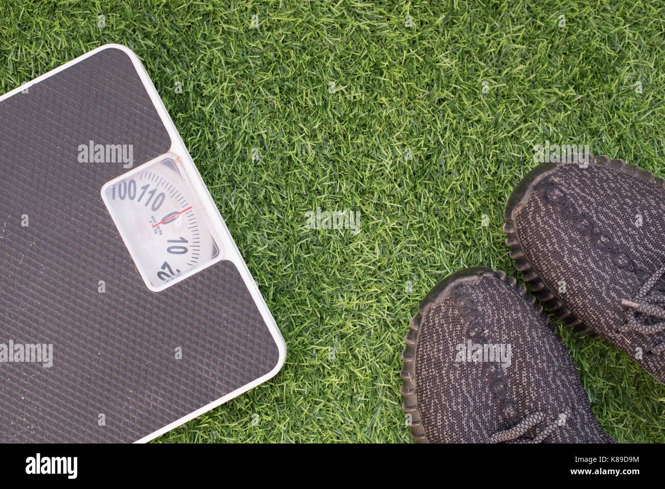 Fitness- und Gewichtsverlust Konzept, weisse Skala und Sport Schuh auf ein Gras, Ansicht von oben, kostenlose Kopie Stockbild