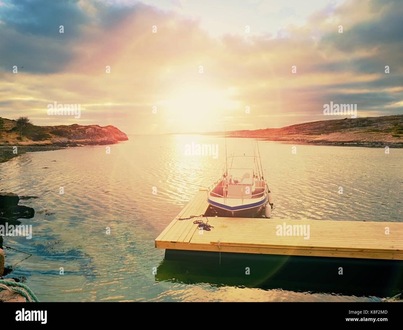 Fischerboot in der Bucht Port, Sonnenuntergang im ruhigen Wasser. Ein Motorboot für die Sportfischerei zu einem Stockbild