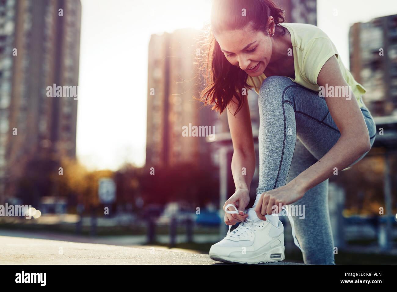 Attraktive Sportlerin Schnürsenkel binden und immer bereit für Fitness Stockbild