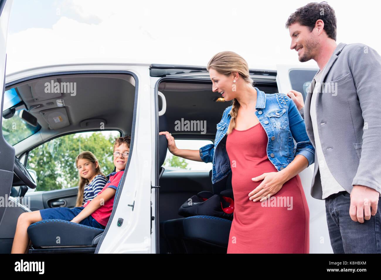Familie kaufen van an Autohändler auf dem Hof Stockbild