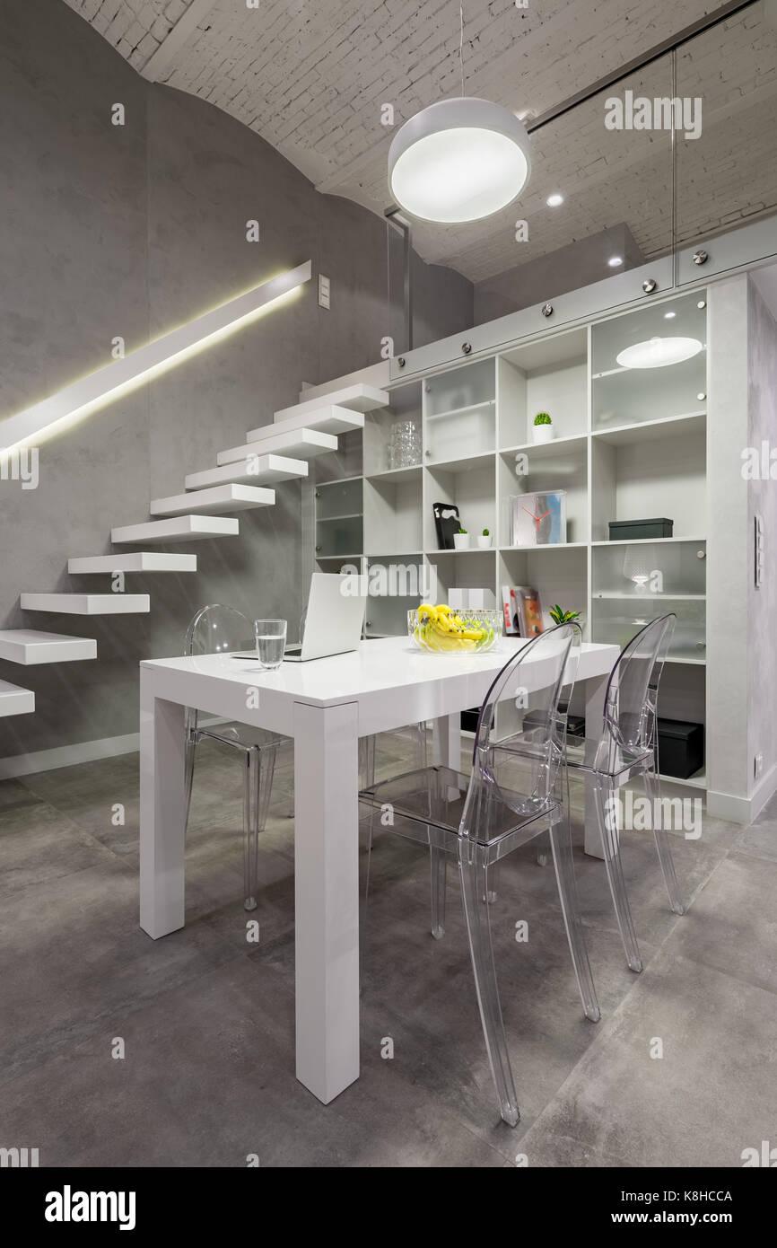 Loft Interieur mit weißer Tisch, transparenten Stühle und Mezzanine ...