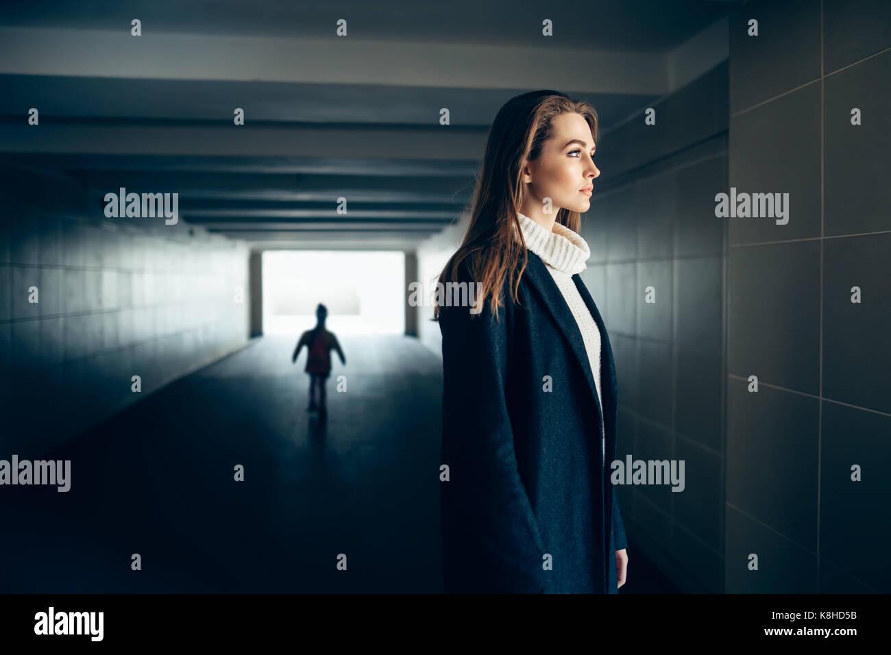 Wunderschöne einsame Frau in einem U-Bahn Tunnel mit erschrecken Silhouette auf Hintergrund. Surrealismus Konzept Stockbild