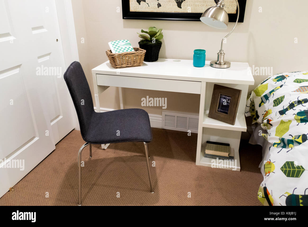 Einen kleinen Schreibtisch mit Lampe und Stuhl in einem Schlafzimmer ...