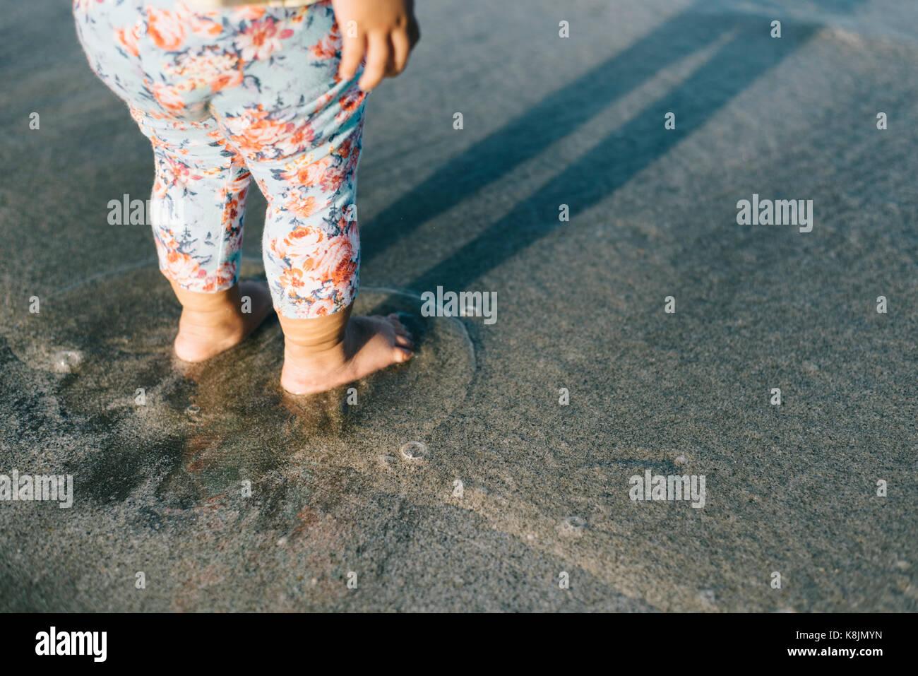 Baby spielt mit Wellen am Strand. Wachstum und Lernen Konzept. Familie und Parenting Konzept Stockbild