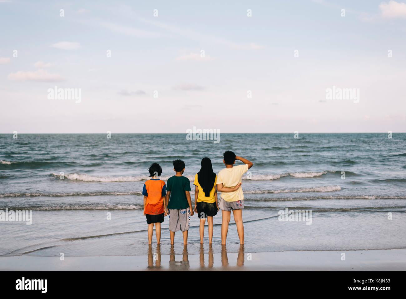Kinder stehen am Strand mit Meerblick. Freundschaft Konzept. Familie Ferien Konzept Konzept. Stockbild