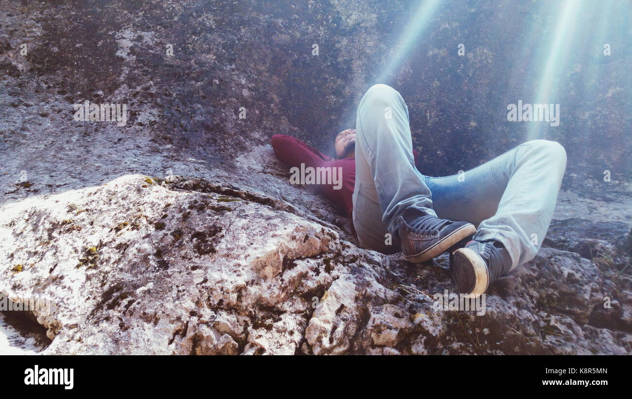 Junger Mann schlafen in einem Berg Stockbild