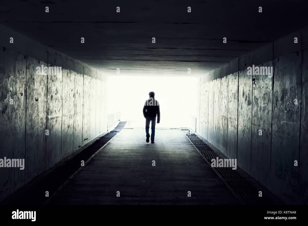 Silhouette in einem u-Bahn-Tunnel. Licht am Ende des Tunnels Stockbild