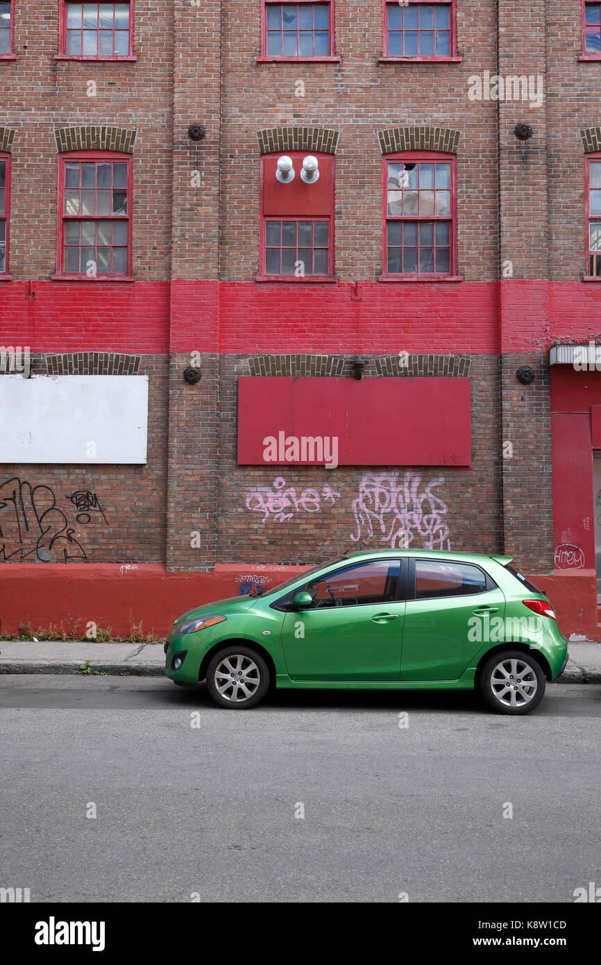 Green Car vor der roten Gebäude geparkt Stockbild