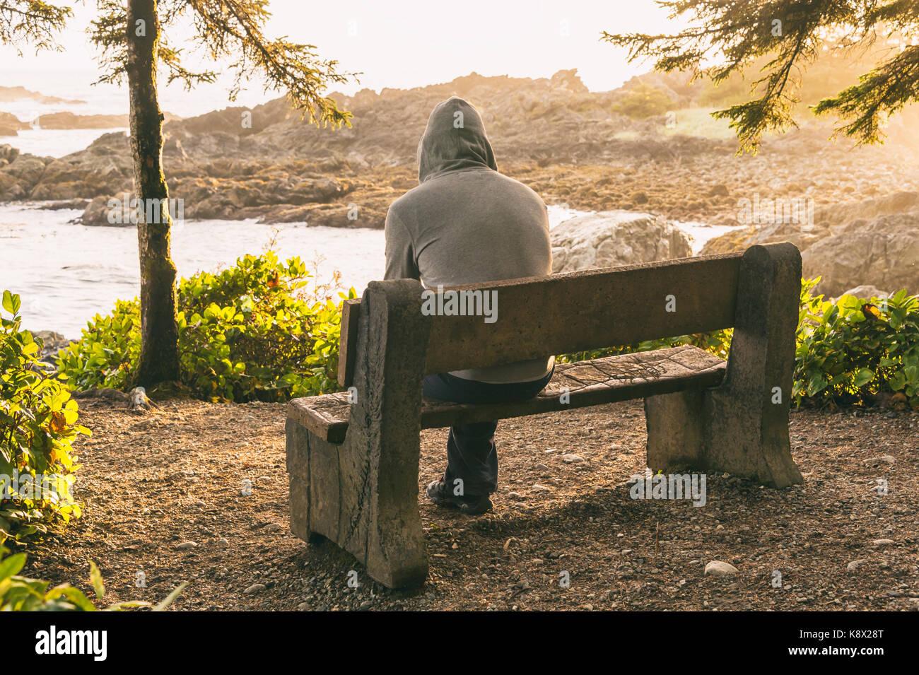 Einsamer Mann sitzt auf der Bank mit Blick auf das Meer auf Vancouver Island bei Sonnenuntergang Stockbild