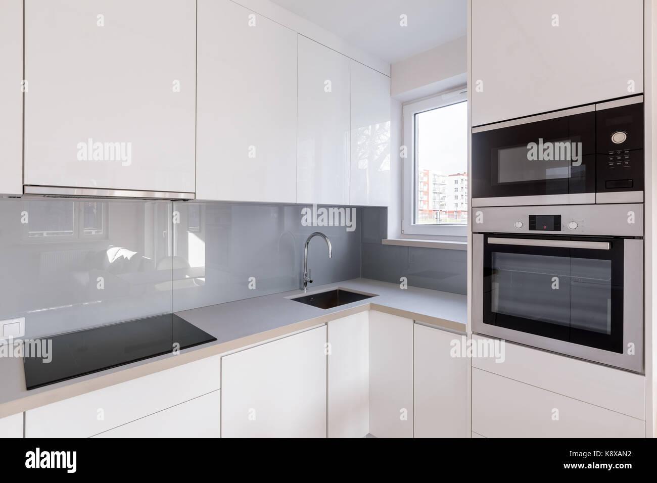 Moderne Küche Mit Weißen Schränke, Hochglanz Fliesen Und Neue Mikrowelle  Und Backofen