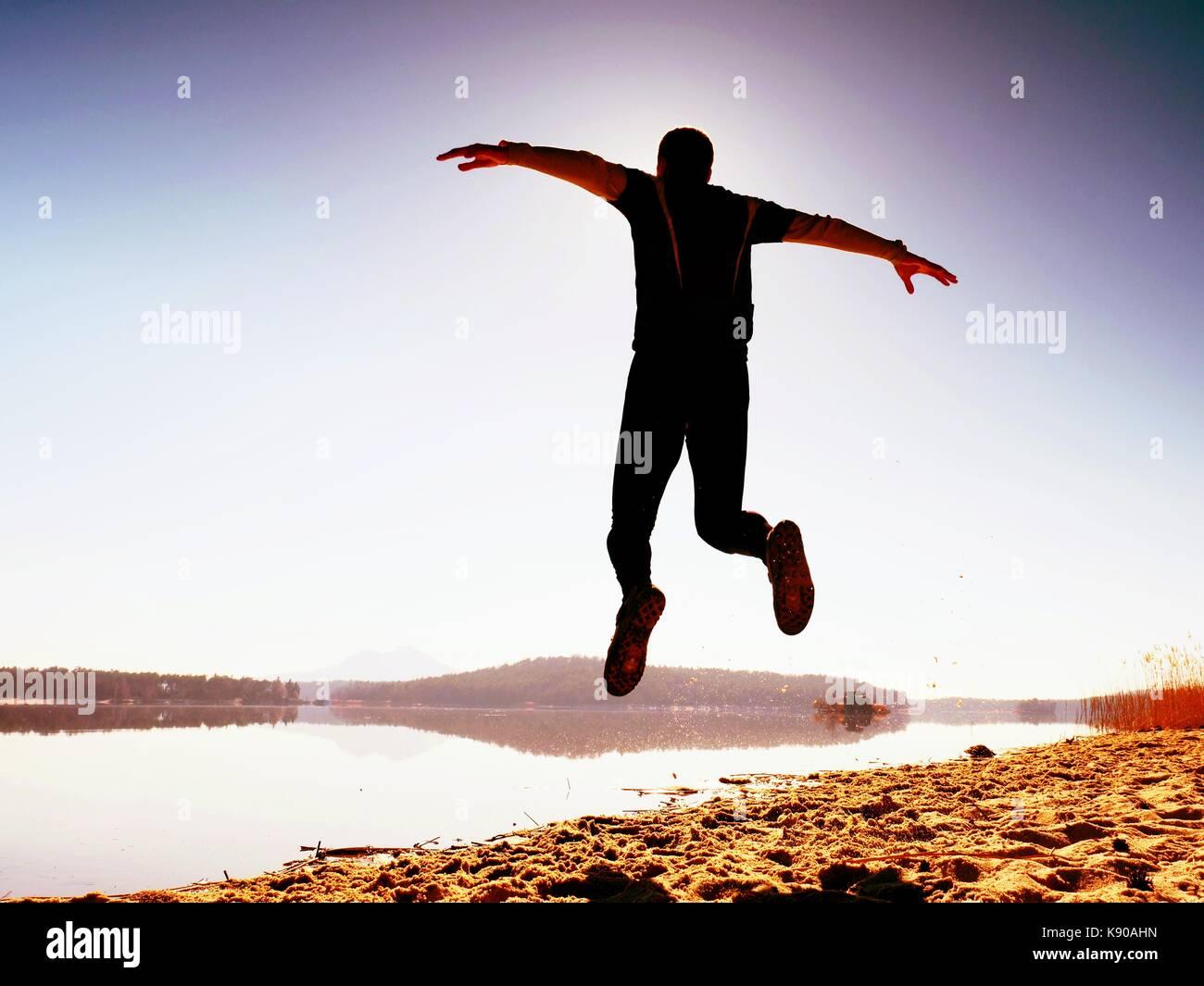 Mann verrückt Springen am Strand. Sportler Fliegen am Strand während der fantastischen Sonnenaufgang über Stockbild