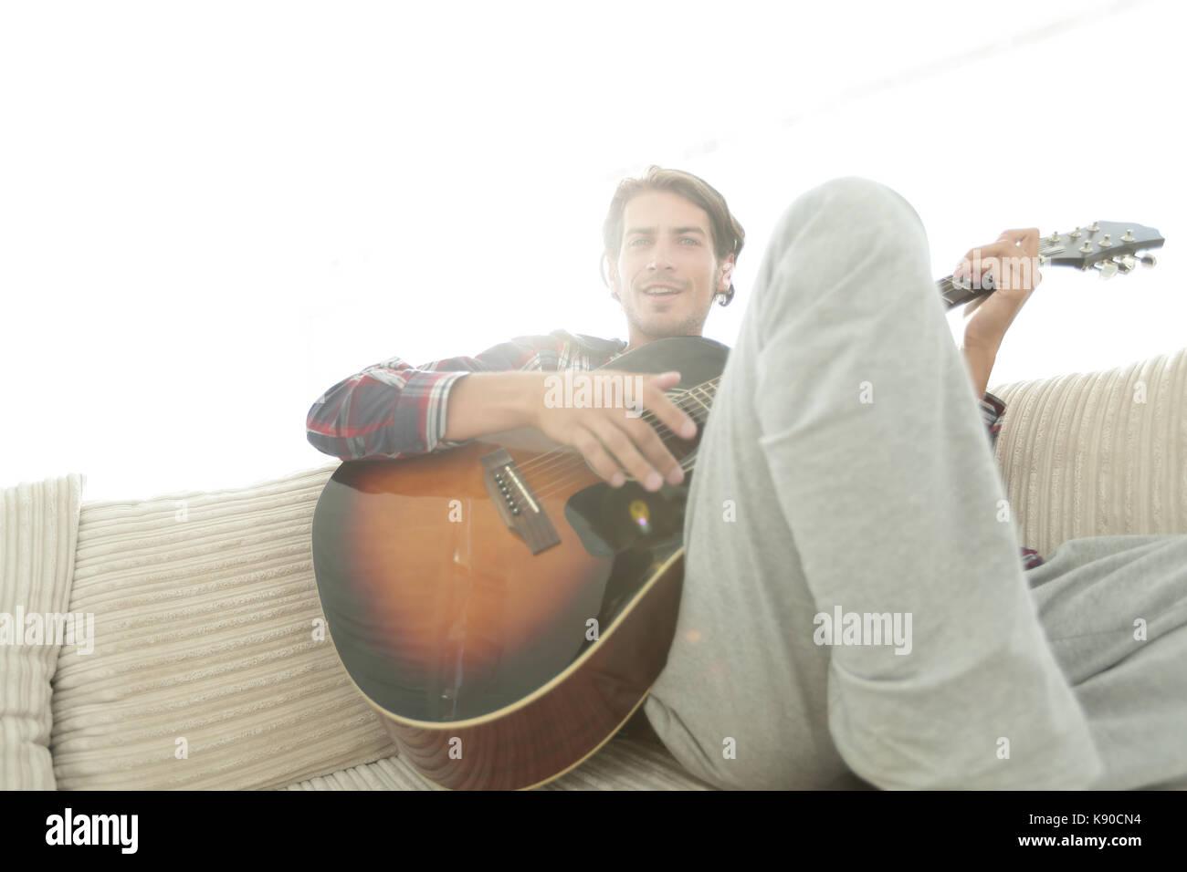 Kerl mit Gitarre sitzt auf einem Sofa im Wohnzimmer. Konzept einer Lebensstil Stockbild