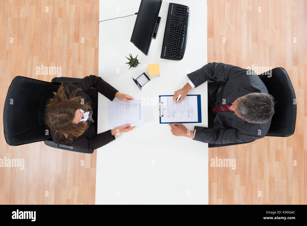 Hohe Betrachtungswinkel der Reifen Geschäftsmann Interviewen weibliche Kandidaten für den Job Stockbild