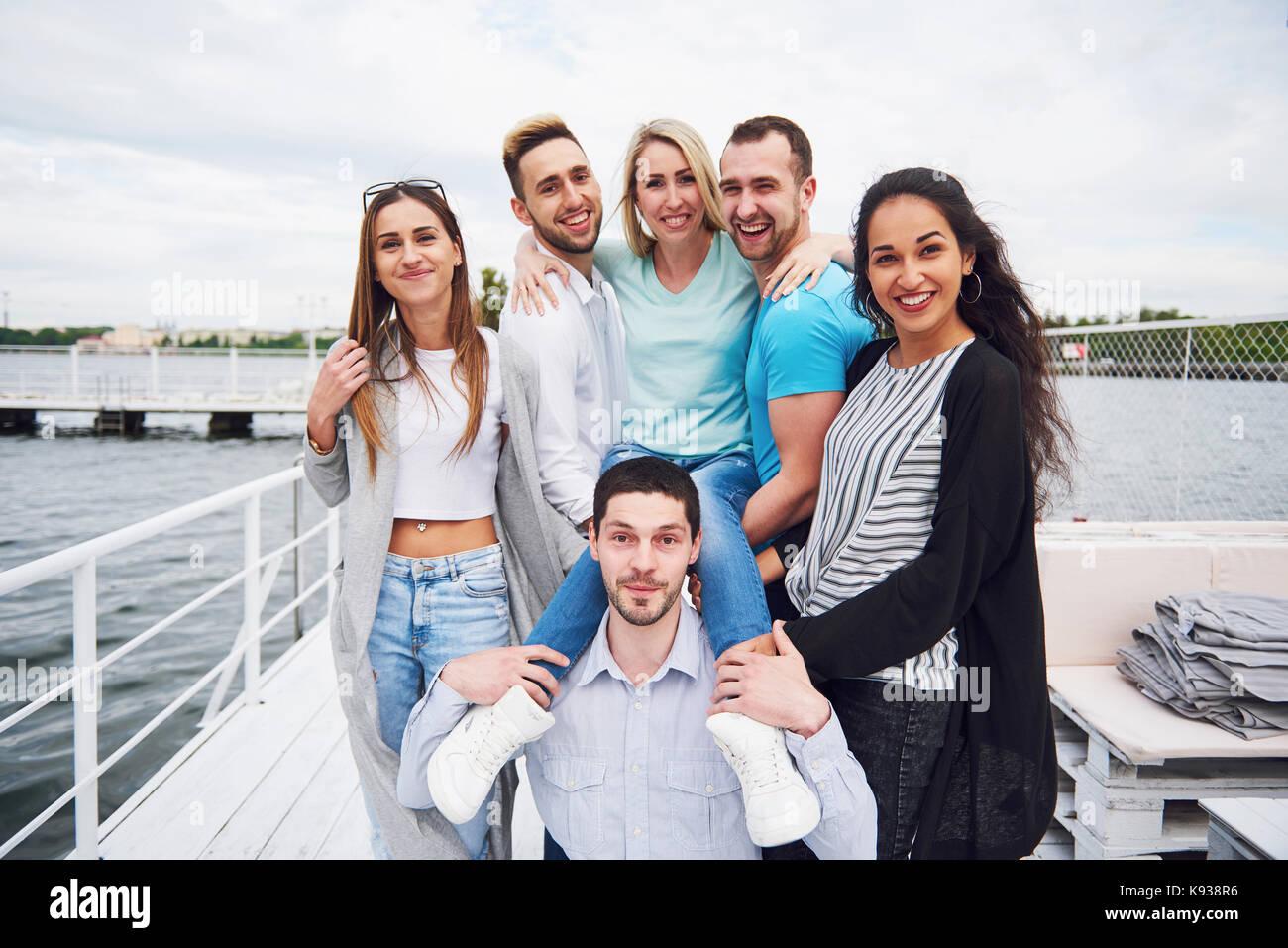 Porträt einer Gruppe junger Leute, die am Rande der Pier, draußen in der Natur. Freunde genießen Stockbild