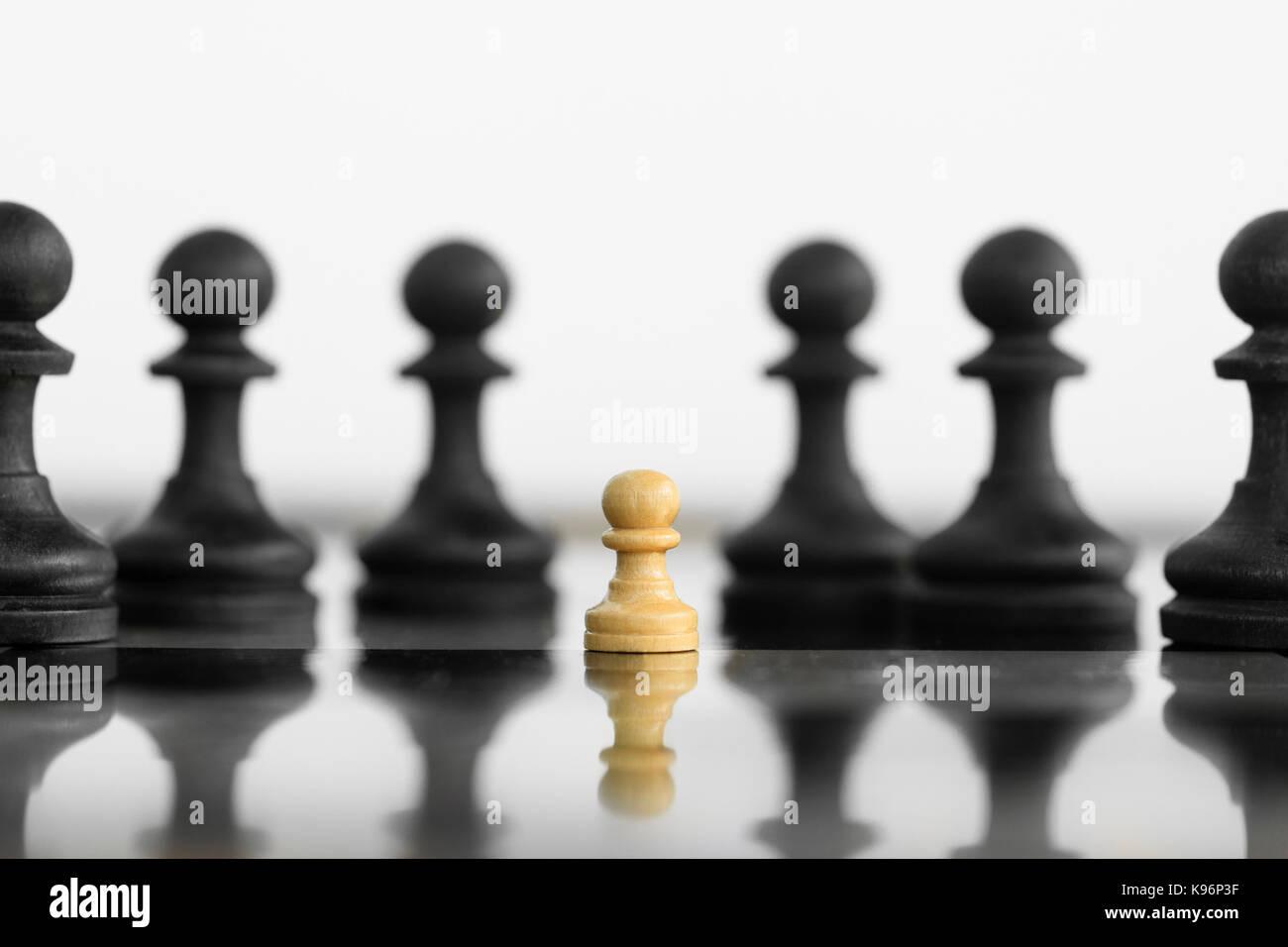 Selbstvertrauen weiß Peon stand vor einer schwarzen Schach Armee vor der Konfrontation. Stockbild