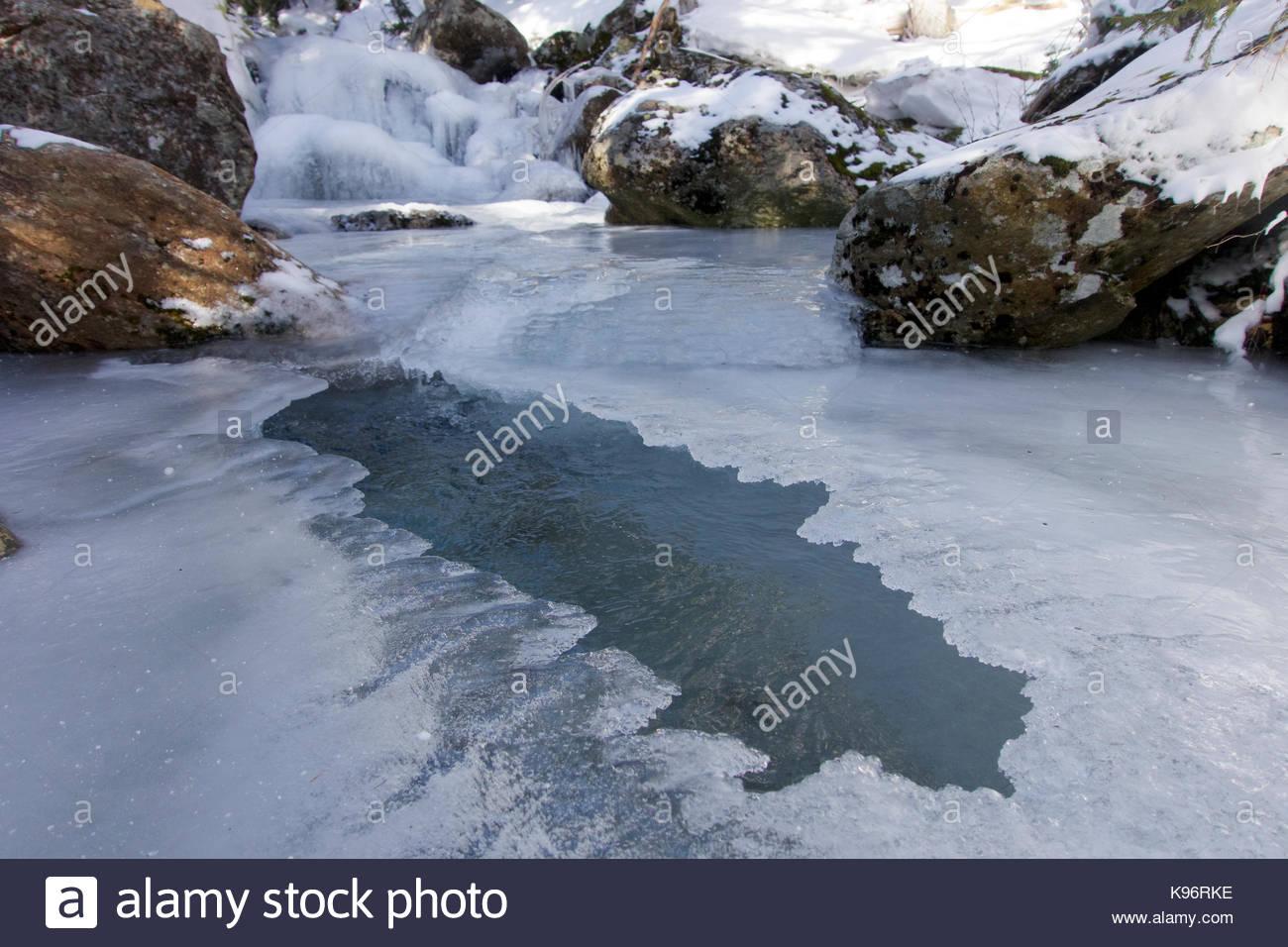 Eine größtenteils gefrorenen Fluss mit Felsen in New England. Stockbild