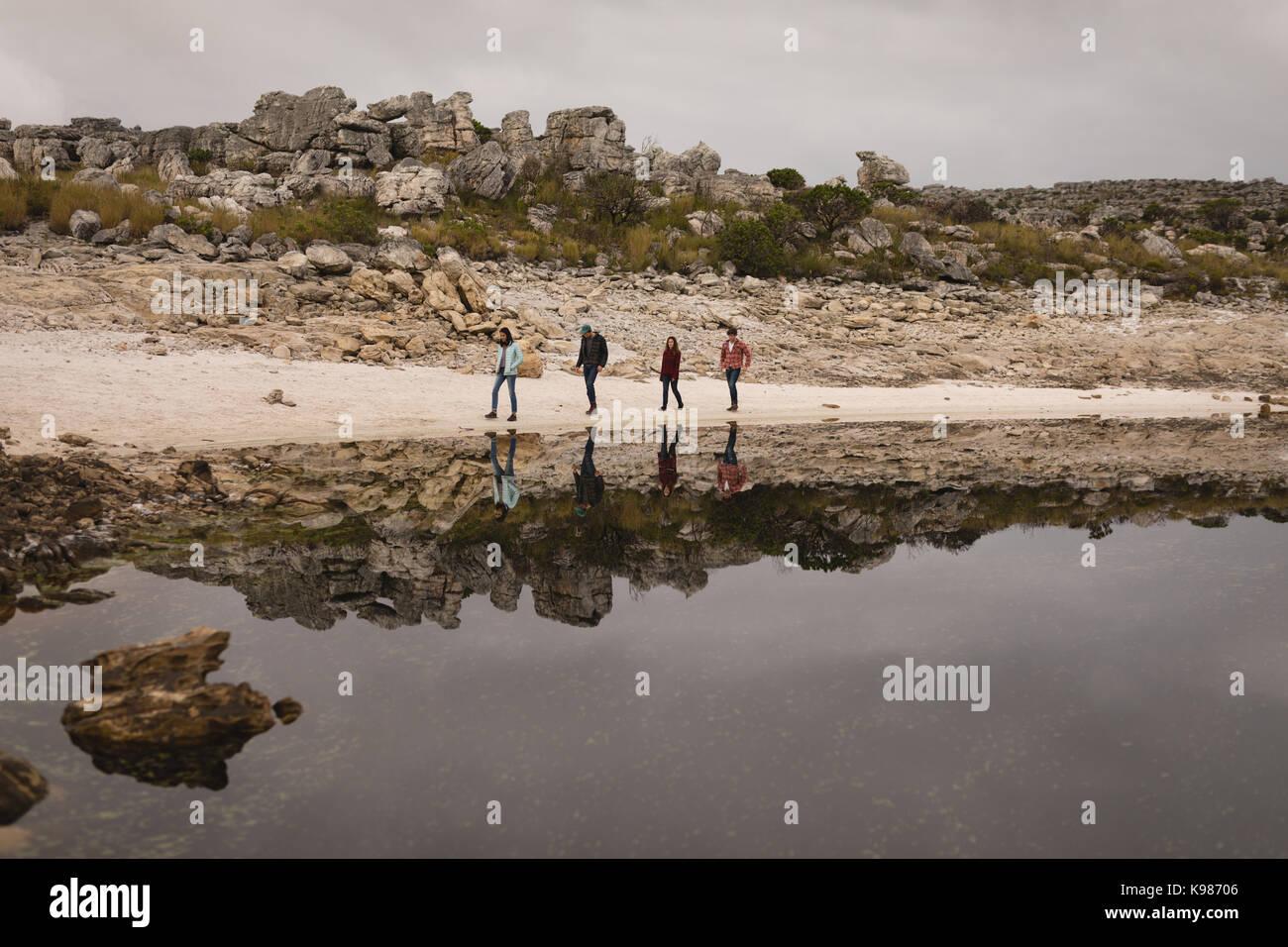 Eine Gruppe von Freunden zu Fuß in der Nähe am See an einem sonnigen Tag Stockfoto