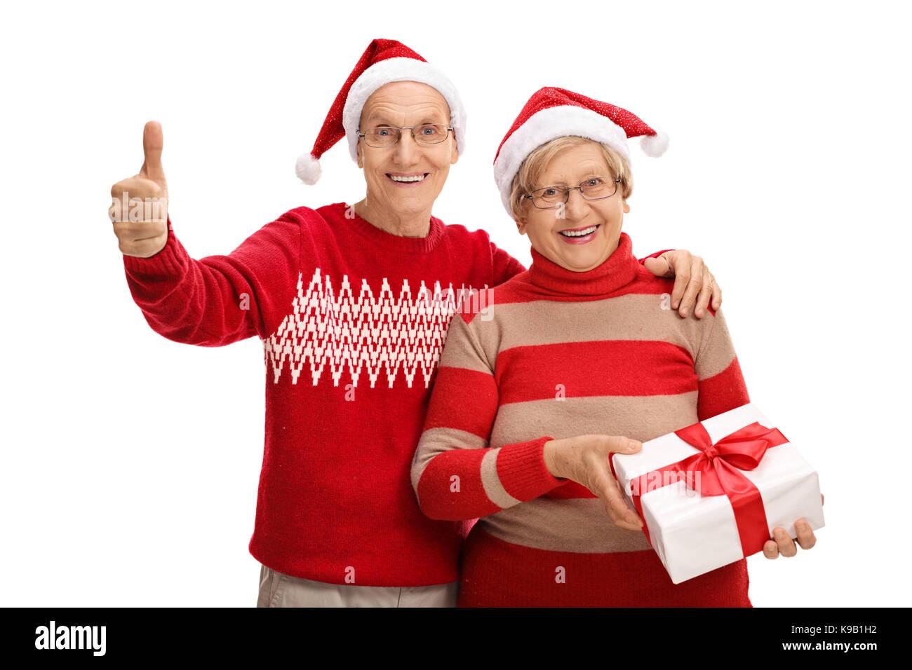 Ältere Paare mit Weihnachten Hüte und ein Geschenk, ein \