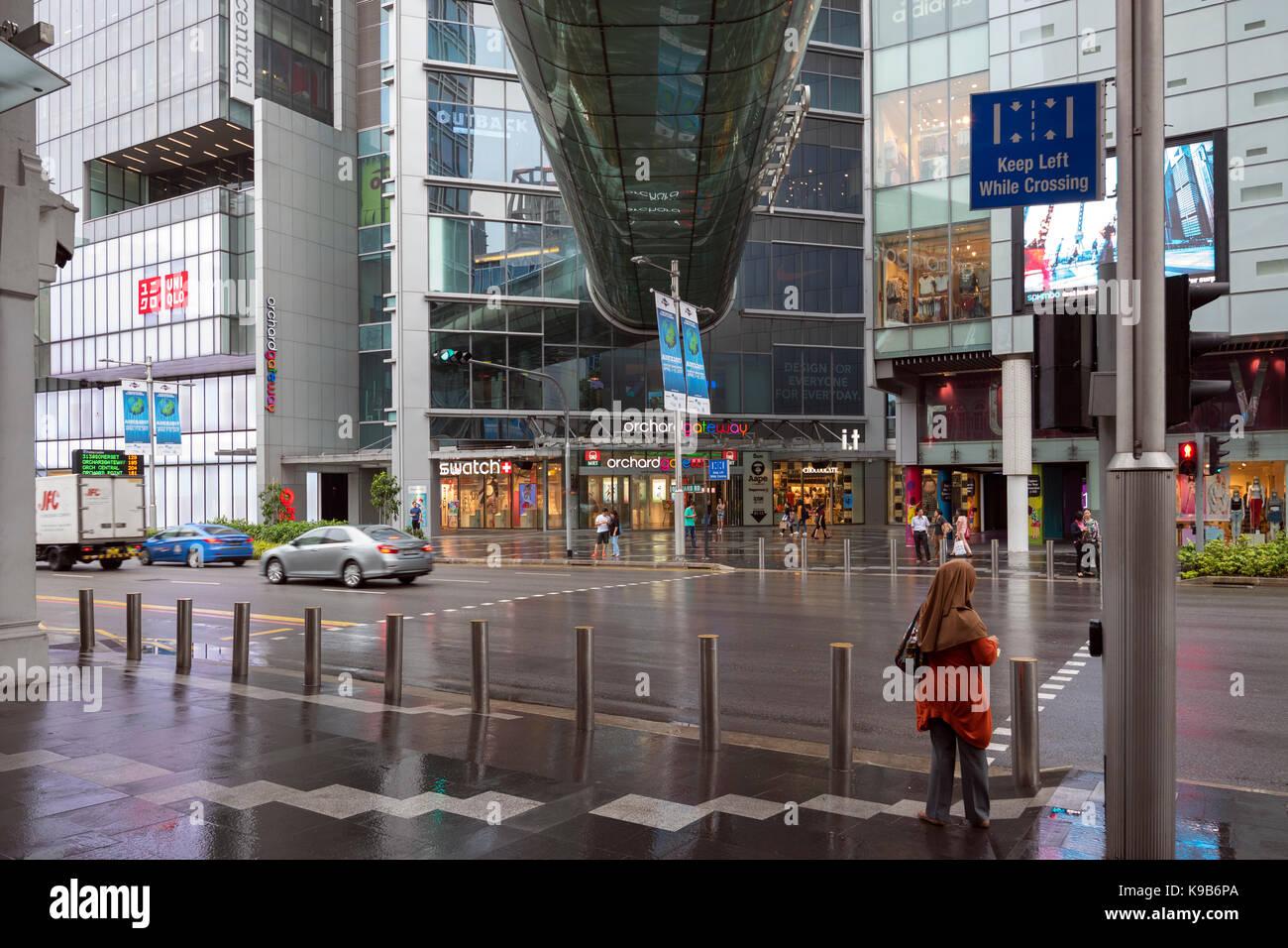 Orchard Road mit Obstgarten - Gateway Shopping Mall und Glas röhrenförmige Brücke zwischen den 2 Stockbild