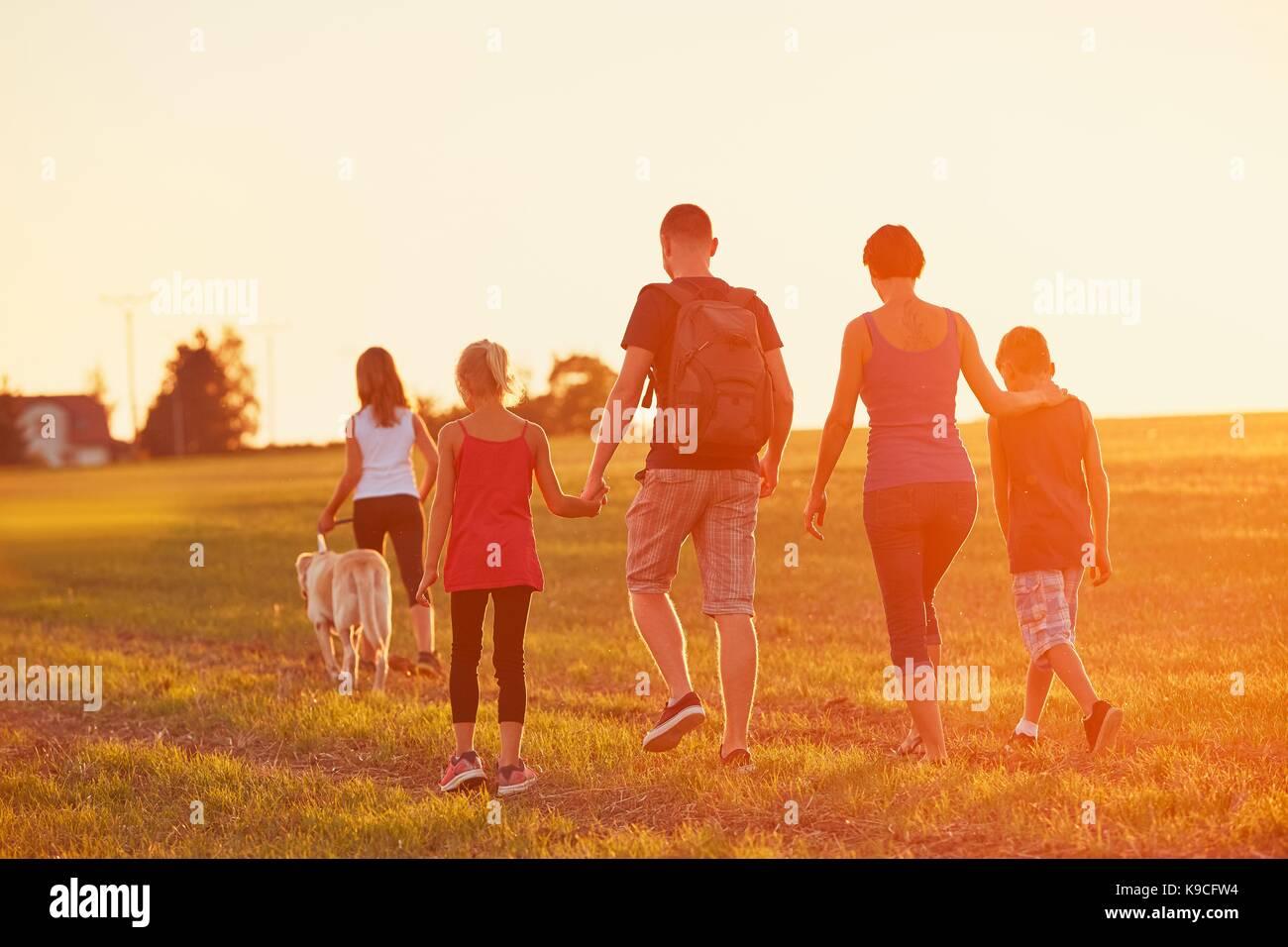 Sommer auf dem Land. Silhouetten der Familie mit Hund auf der Fahrt in den Sonnenuntergang. Stockbild
