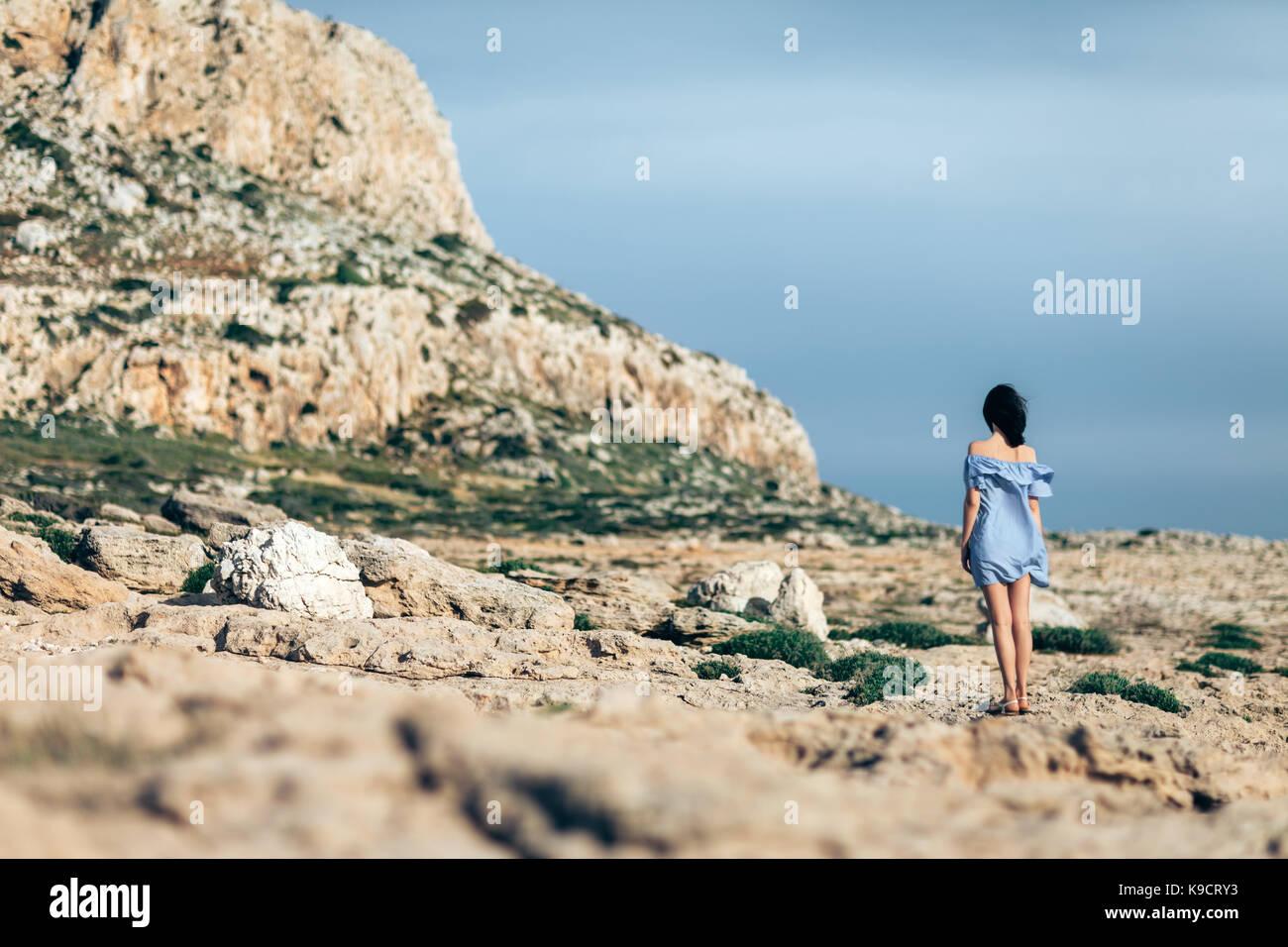 Zurück Blick auf einsame Frau zu Fuß auf steinige Wüste mit dramatischen Himmel Stockbild