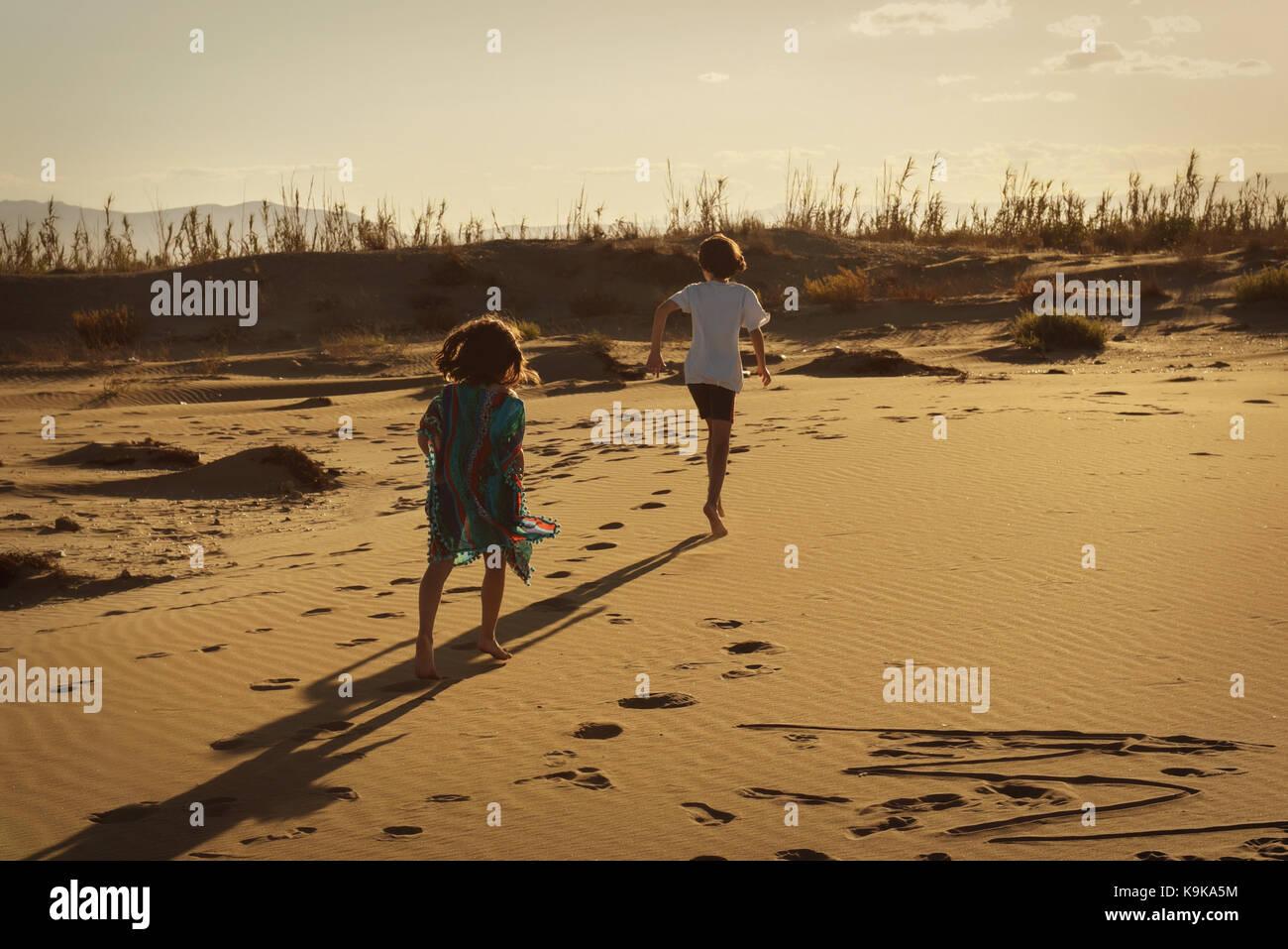 Junge und Mädchen Running Wild auf einem sandigen Strand bei Sonnenuntergang verlassen Footprints Stockbild