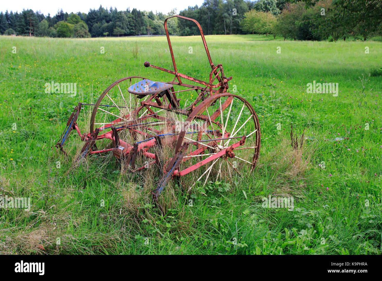 Ändern, rostiger Traktor, Mähdrescher auf einer Wiese, einem Feld Stockbild