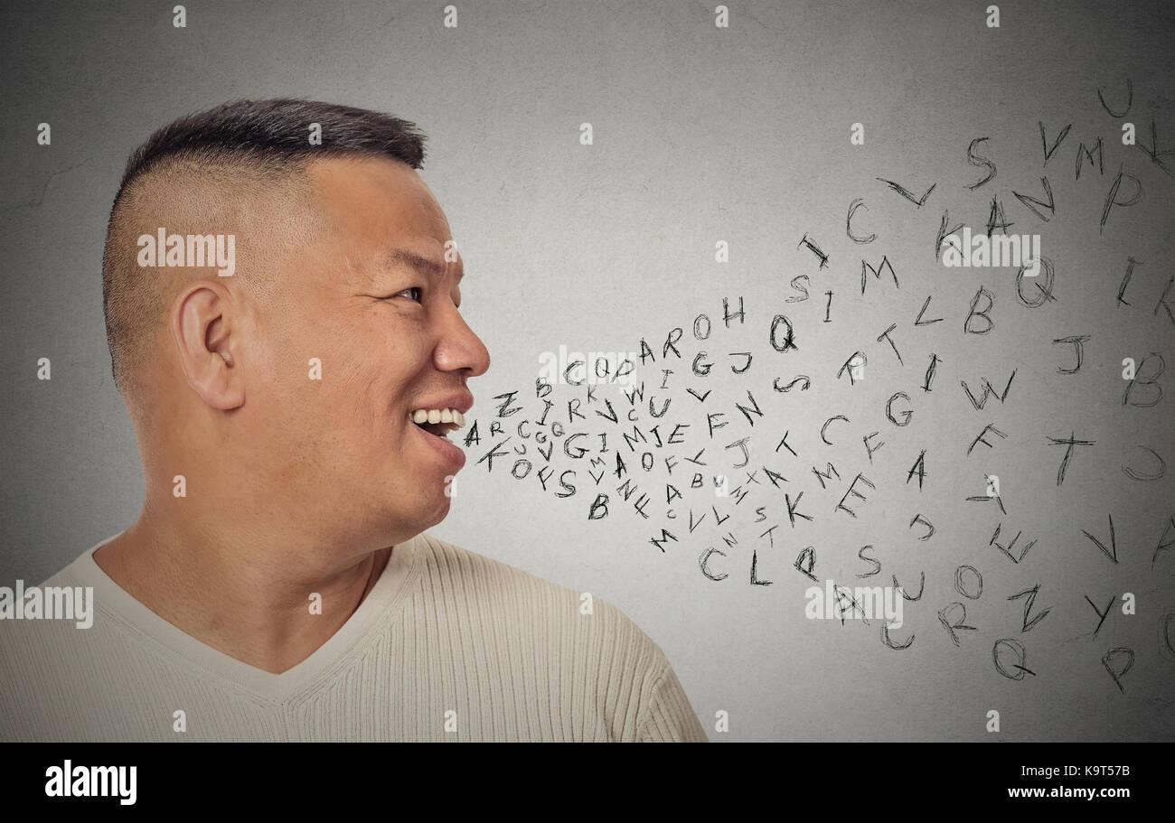 Seitenansicht Porträt junger stattlicher Mann mit Buchstaben des Alphabets aus offenen Mund isoliert grauen Stockbild