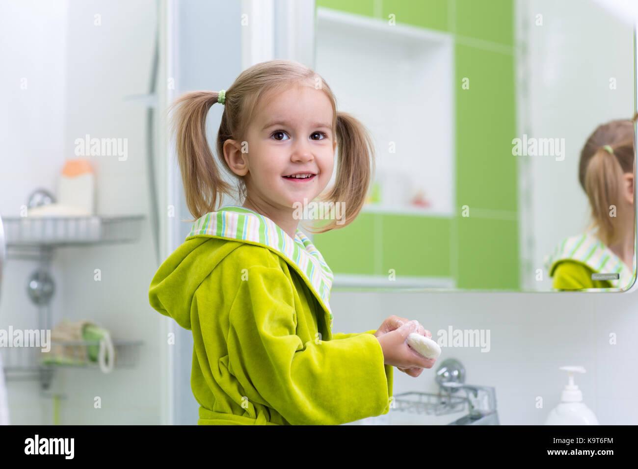 Niedliche Kind kleines Mädchen mit Pferdeschwanz in grün Bademantel ihre Hände waschen im Bad Stockbild