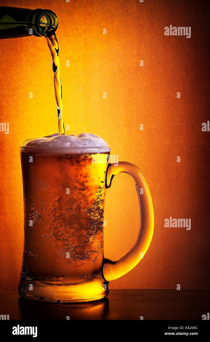 Leckere kalte Bier gezapft aus der Flasche in das Glas über orange ...