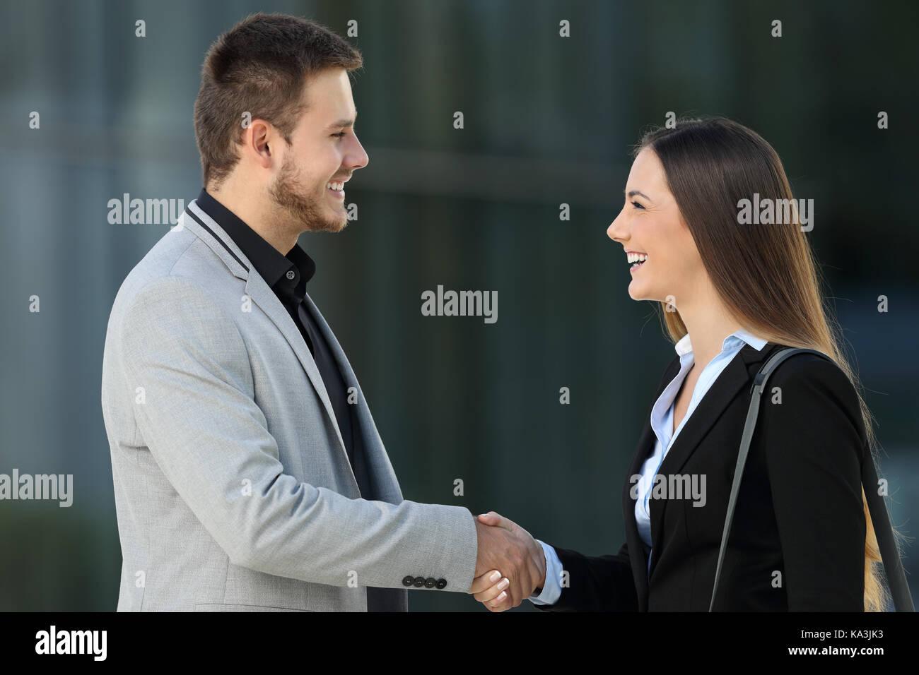 Seitliche Sicht auf zwei Glückliche Führungskräfte treffen und Handshake auf der Straße mit einem Bürogebäude im Stockfoto