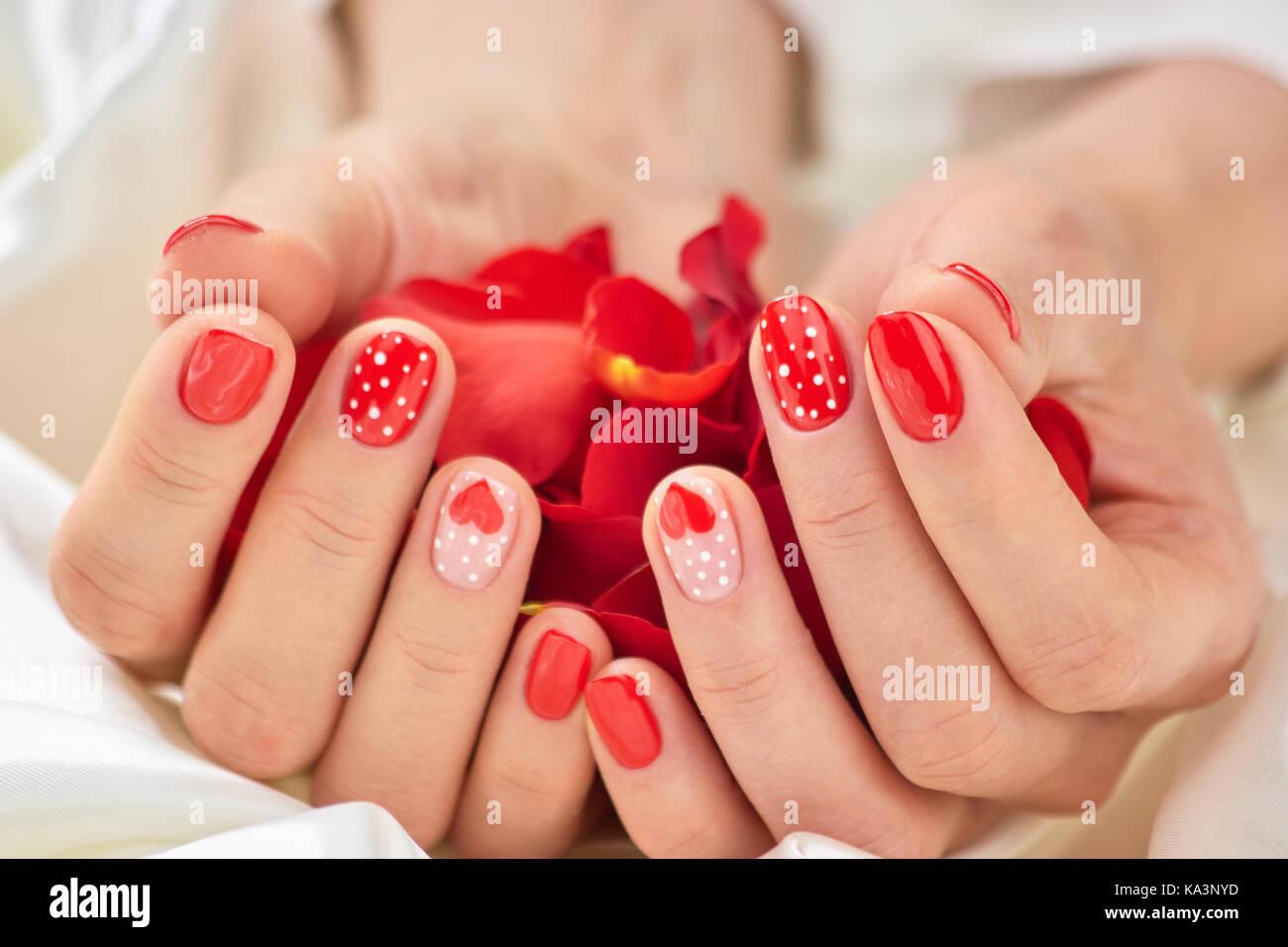 Rot romantisch Maniküre und Blütenblätter. Schöne Hände mit ...