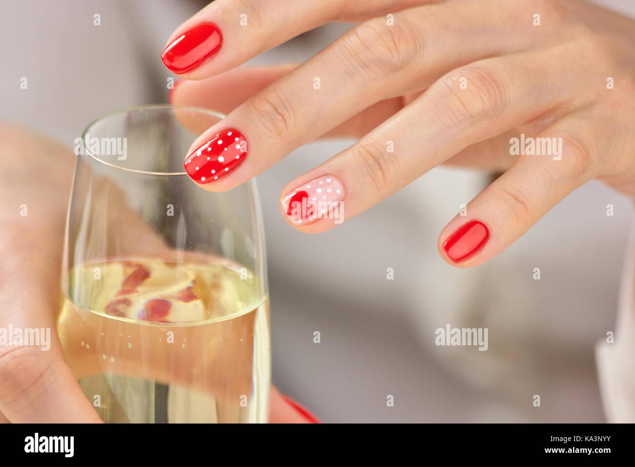 Weibliche gepflegten Hände und Champagner. Junge Frau Hände mit ...