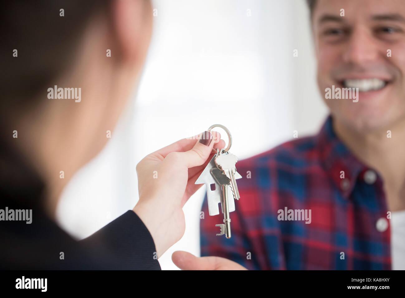 Man Schlüssel zum neuen Haus sammeln von weiblichen Realtor Stockbild