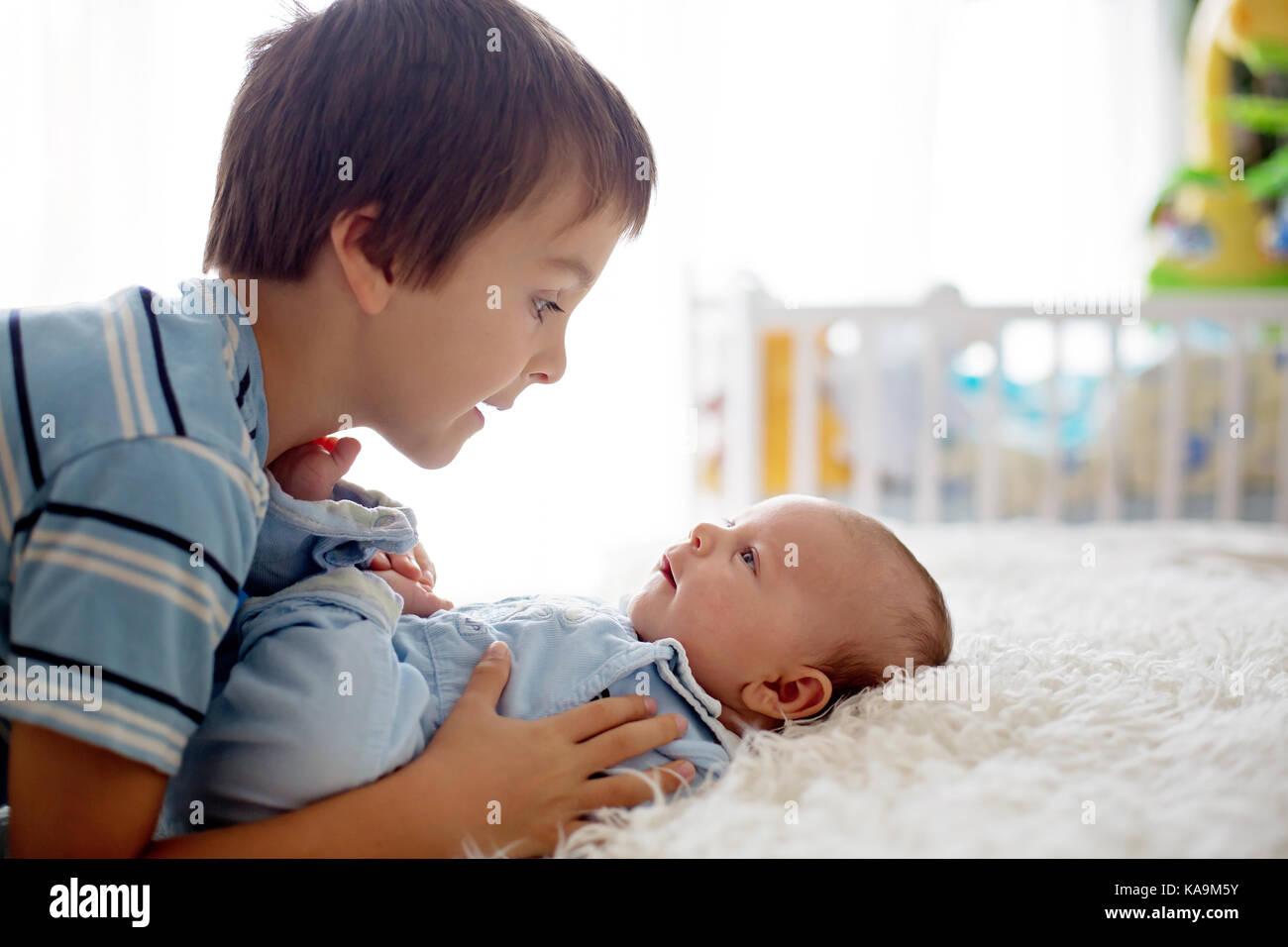 Schöne junge, umarmen mit Zärtlichkeit und sein neugeborenes Baby Bruder Pflege zu Hause. Familie Liebe Stockbild