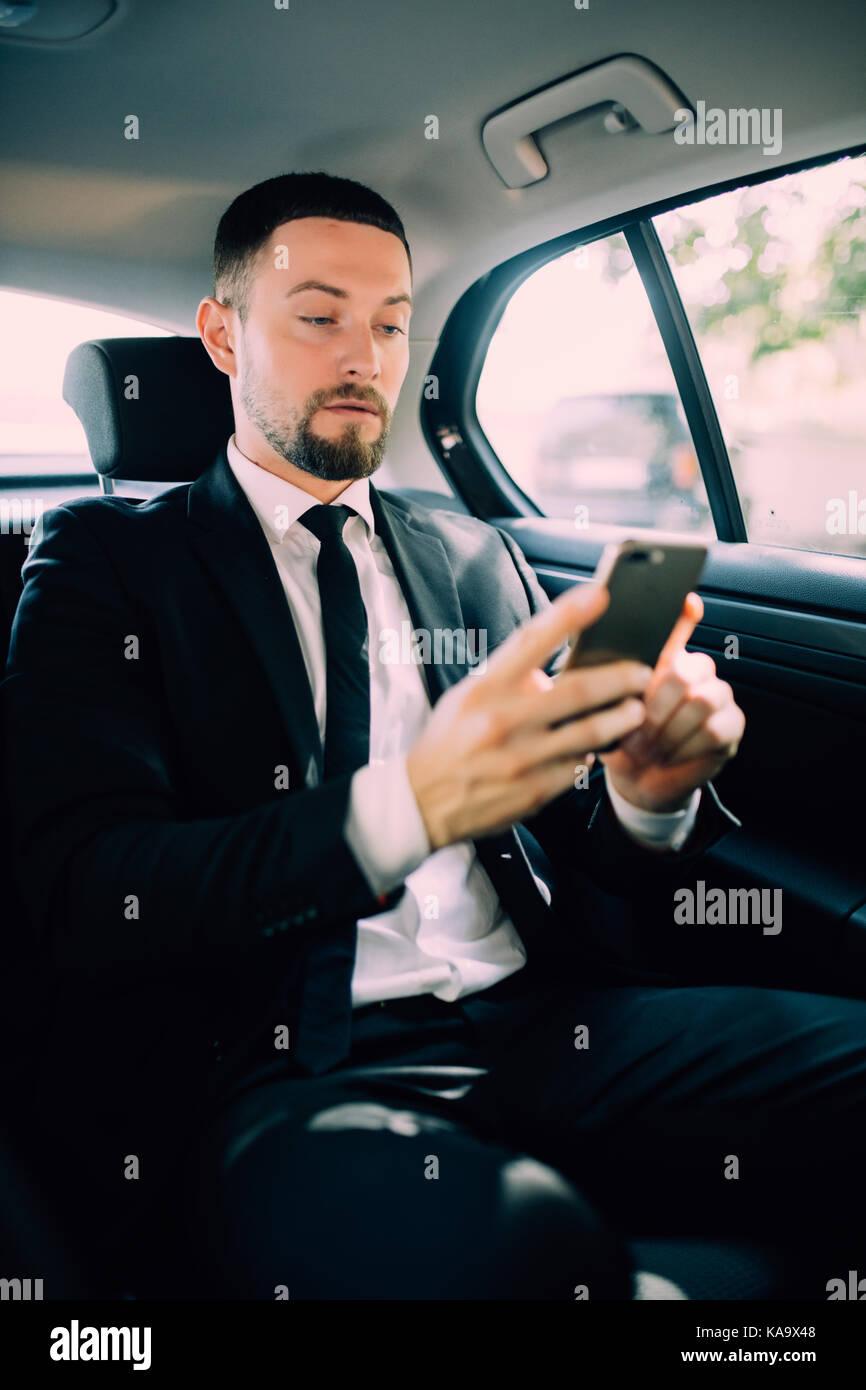 Ein Geschäftsmann auf Reisen mit dem Auto auf dem Rücksitz, eine Nachricht oder E-Mails und Anrufe senden. Stockbild