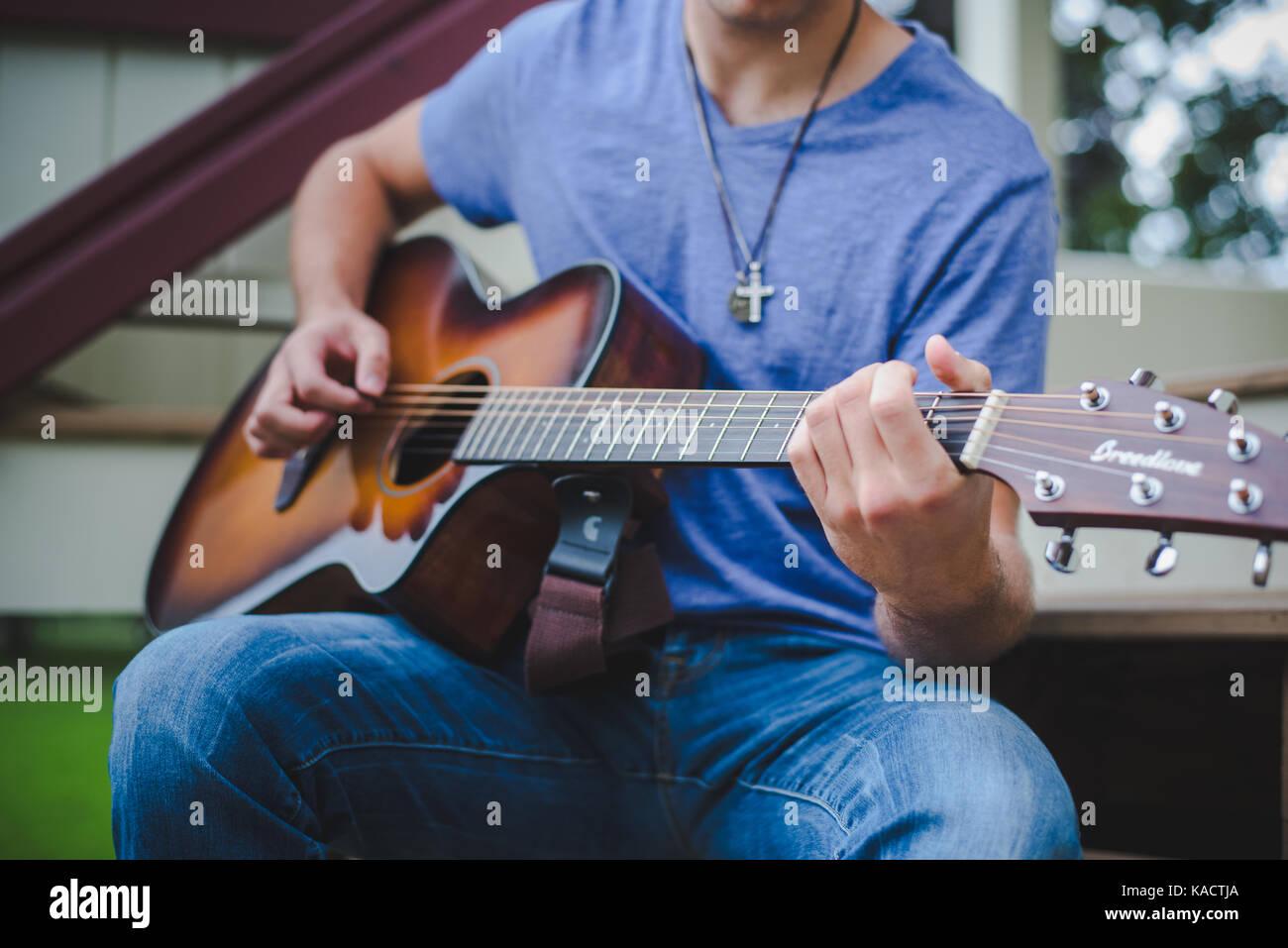 Ein junger Mann spielt eine Gitarre. Stockfoto