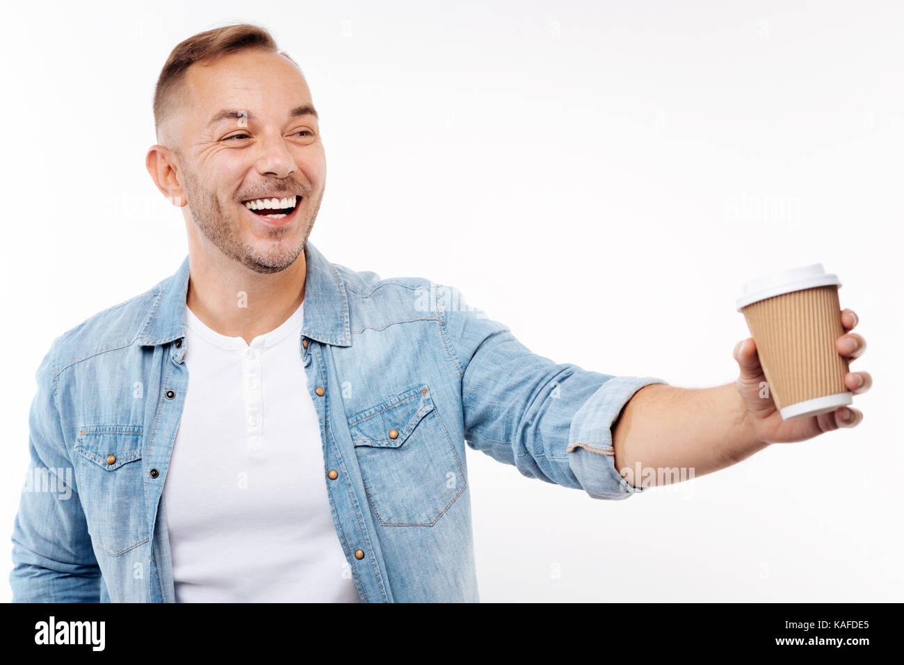 Fröhlicher junger Mann mit einem Papier Tasse Kaffee Stockbild