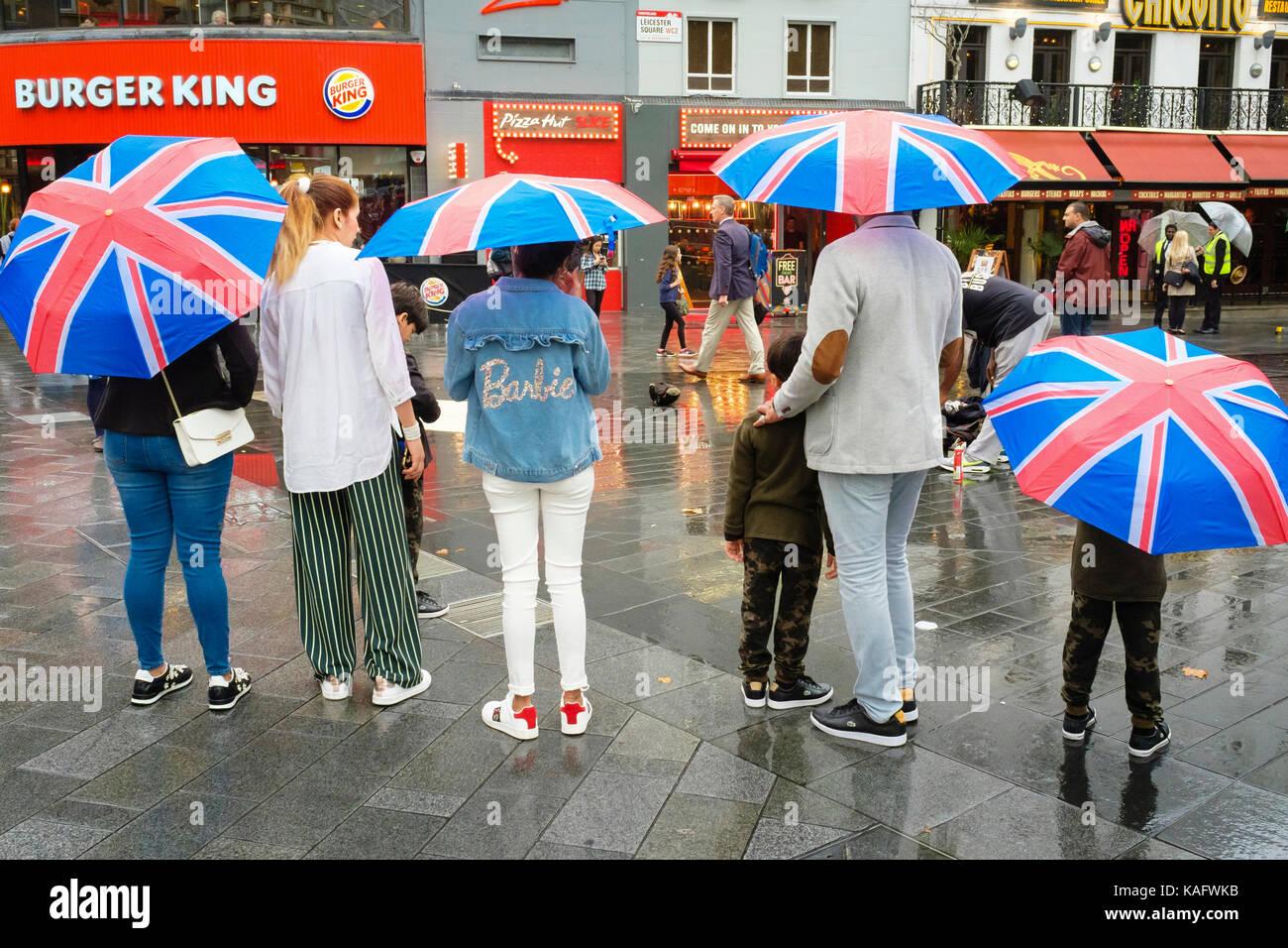 Touristen mit Union Jack Schirme, Leicester Square, London, UK Stockbild