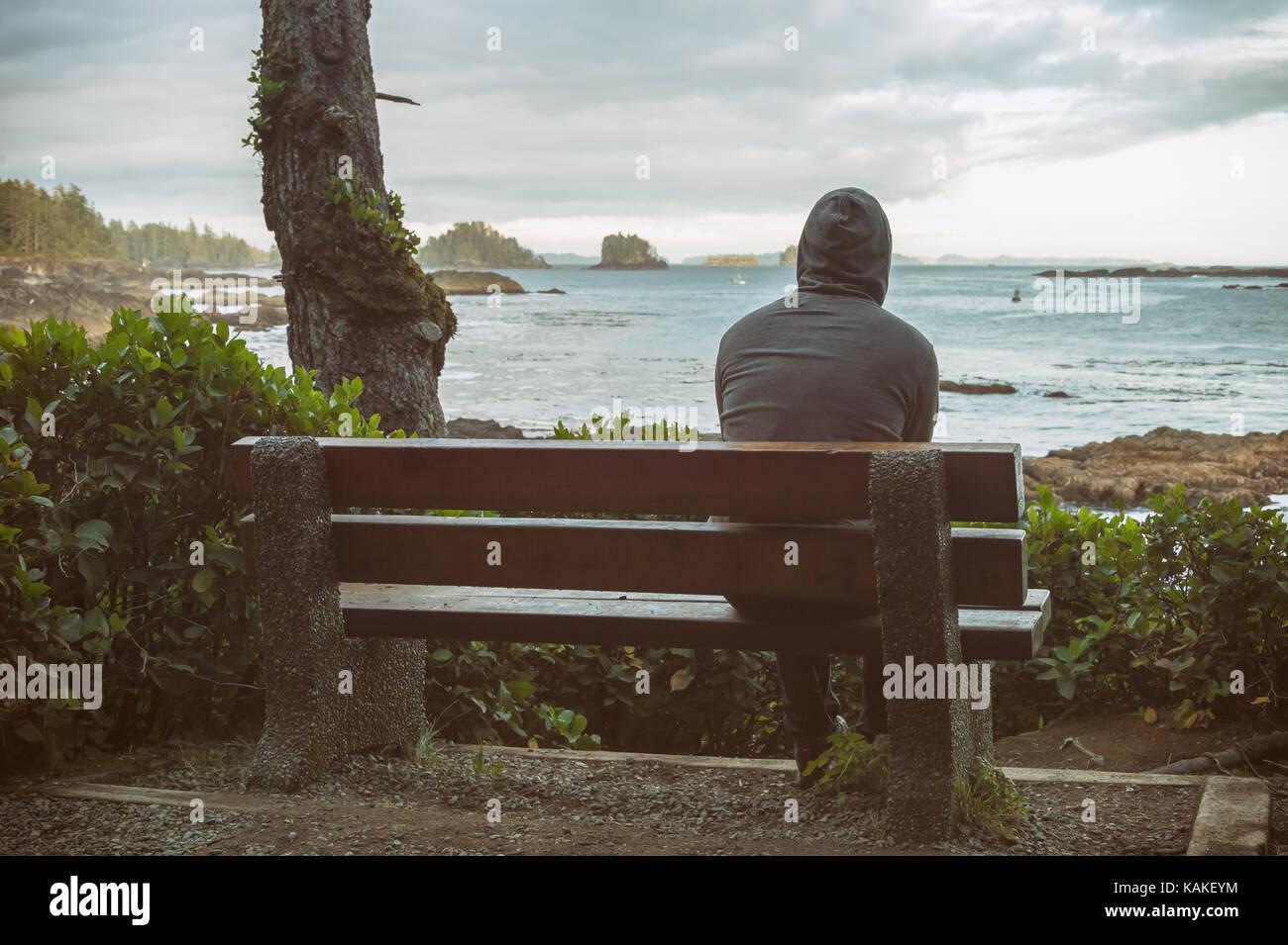 Traurig und einsam Mann sitzt auf der Bank mit Blick auf das Meer auf Vancouver Island Stockbild