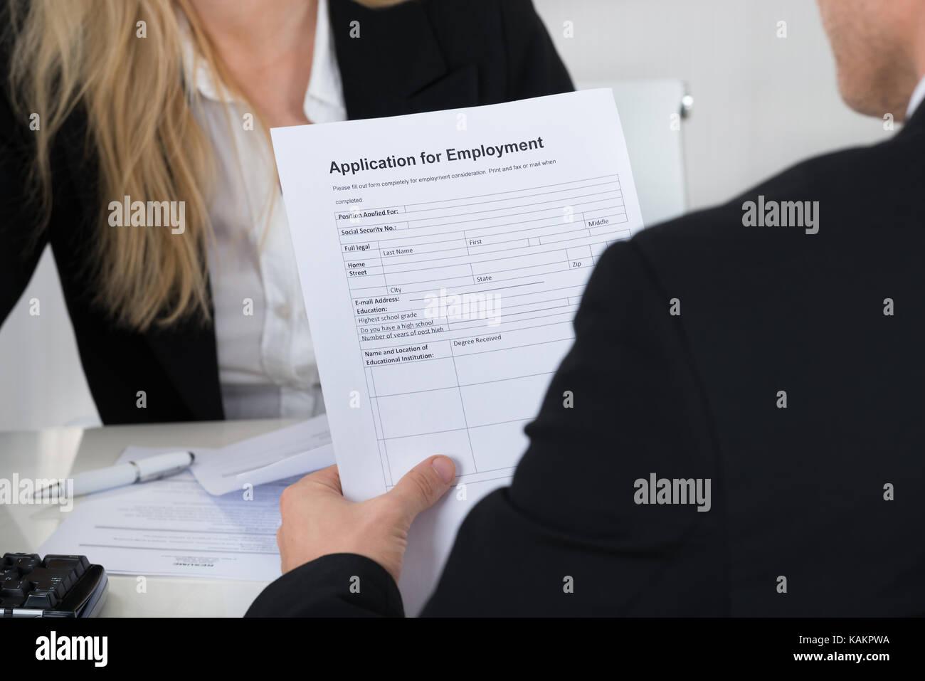 Männliche Bewerber holding Antrag vor der Interviewer im Büro Stockbild