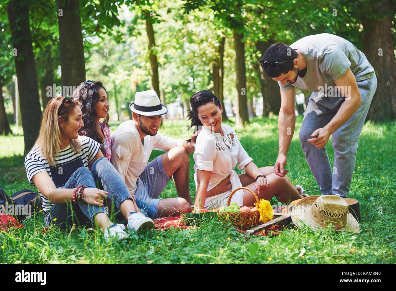 Gruppe von Freunden mit Picknick in einem Park an einem sonnigen Tag - Leute rumhängen, Spaß, Grillen und entspannen Stockfoto