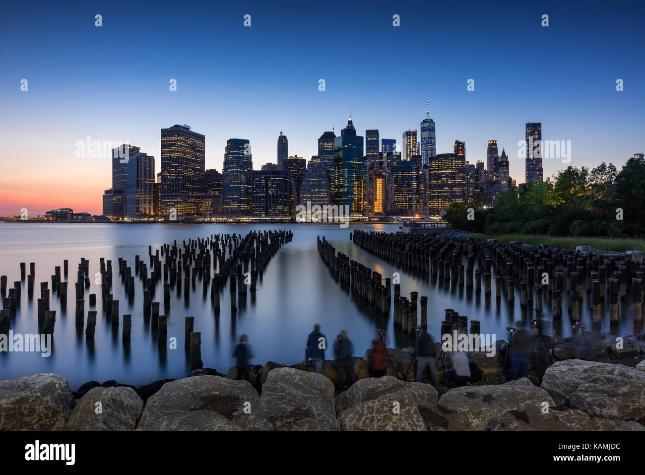 Wolkenkratzer von Manhattan bei Sonnenuntergang und Holz-pilings aus Brooklyn Bridge Park. Manhattan, New York City Stockbild