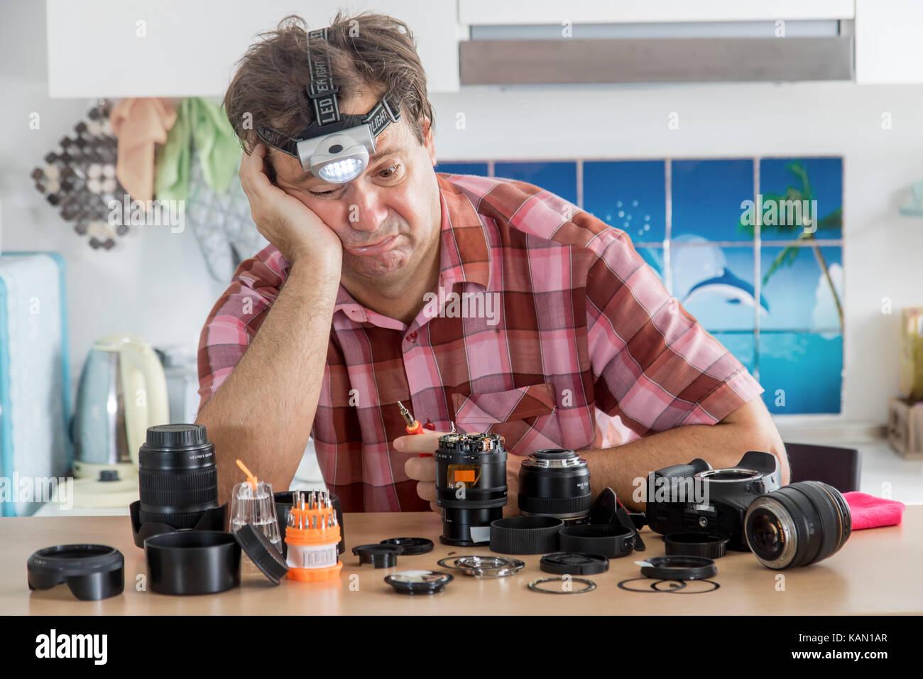 Amateur Fotograf versucht sein Objektiv zu reparieren. Ein hobby Amateur das Gerät einer digitalen Kamera reinigt. Stockbild