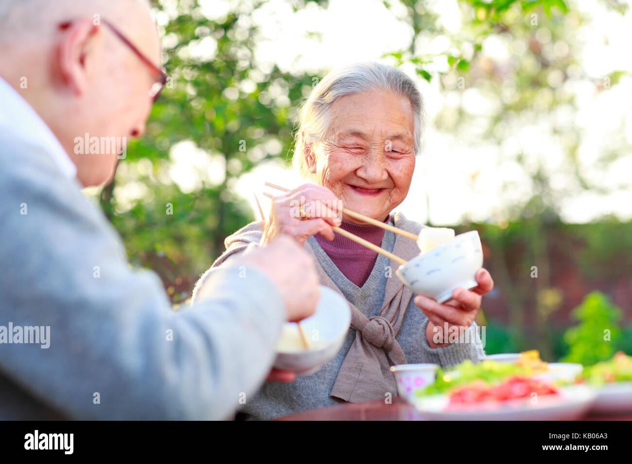 Glückliche und gesunde chinesische senior Paar zusammen essen im Garten Stockbild