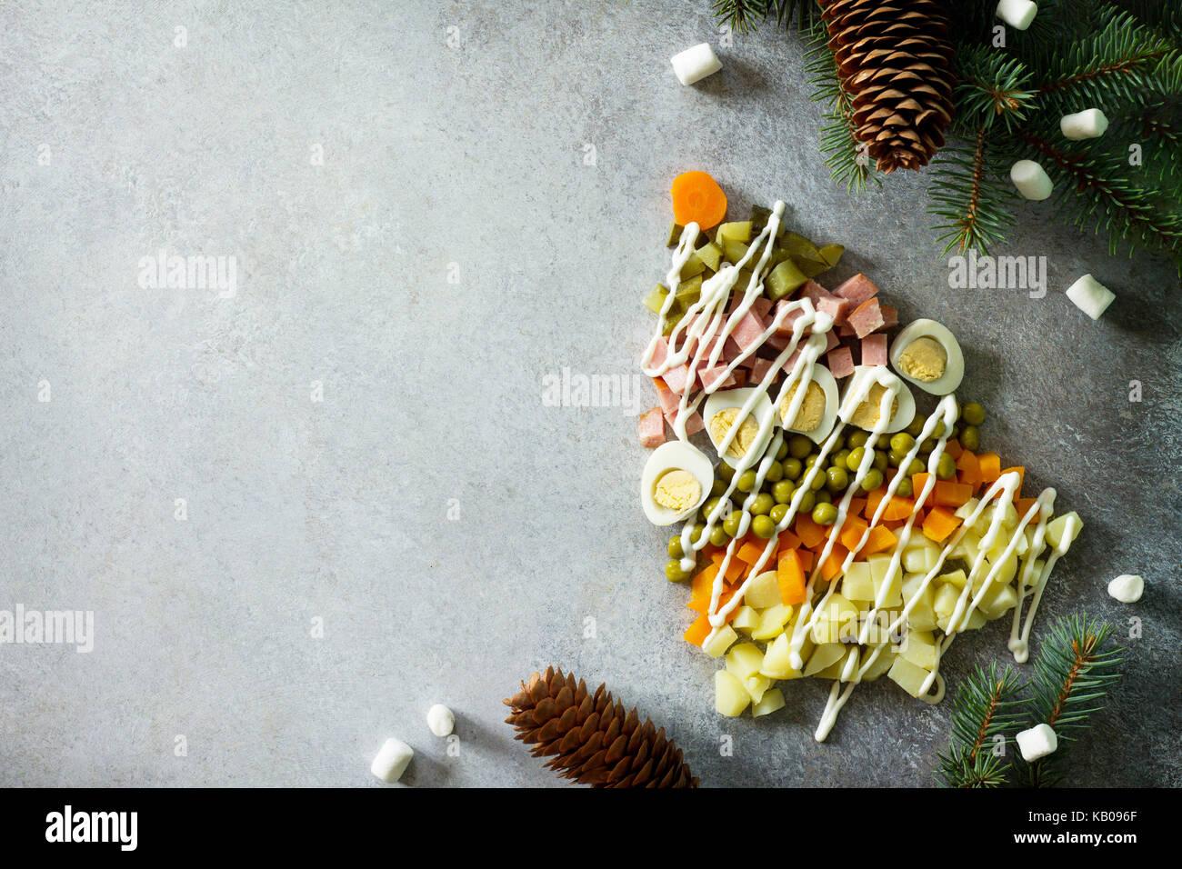 Weihnachtsbaum aus Salat Olivier auf grauem Schiefer, Stein oder Metall Hintergrund. Schöne Weihnachten und Stockbild